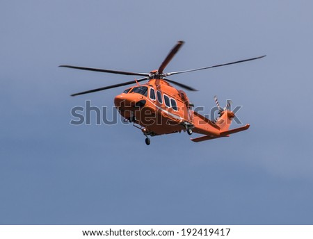 Orange helicopter is flying