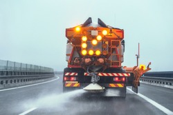 Orange highway maintenance gritter truck spreading de-icing salt on road in winter.
