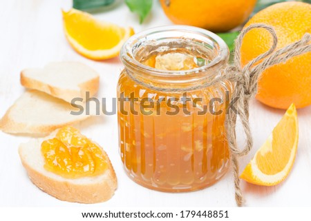 orange jam in a glass jar and fresh bread, close-up