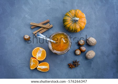 Orange jam in glass jar, pumpkin, oranges, nuts and spices on dark blue gray background #576266347