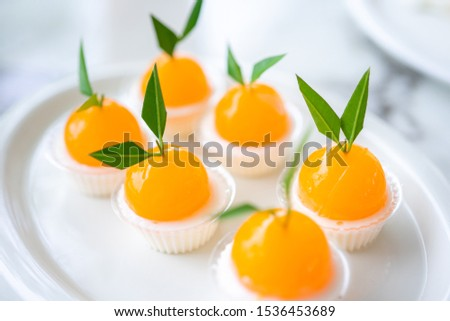 Orange jellies are decorated on a plate of orange-like characteristics. Has a sweet and sour taste