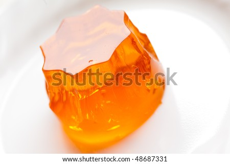 orange jello on white plate, close-up