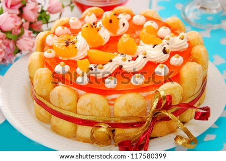 orange jelly and whipped cream torte garnished around with sponge fingers in charlotte style