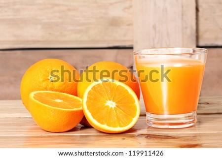 Orange juice and slices on wood