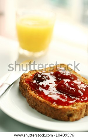 Orange juice and toast with strawberry jam in a kitchen for breakfast