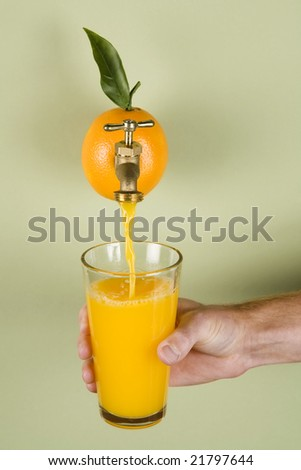 Orange juice being poured into a glass from an actual orange