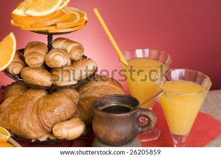 Orange juice, croissants, coffee  close-up on red background.