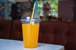Orange juice in box with drinking can on table