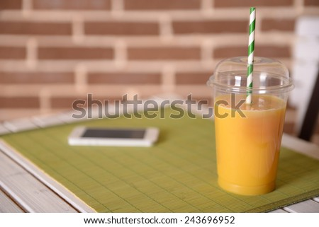 Orange juice in fast food closed cup with tube and mobile phone on wooden table and brick wall background