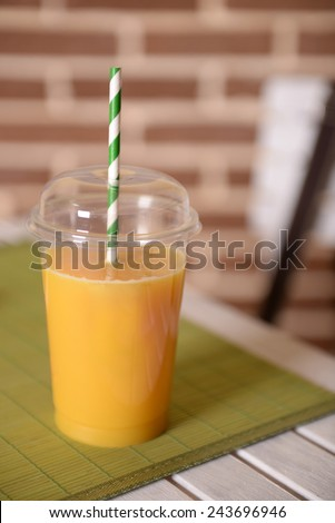 Orange juice in fast food closed cup with tube on wooden table and brick wall background