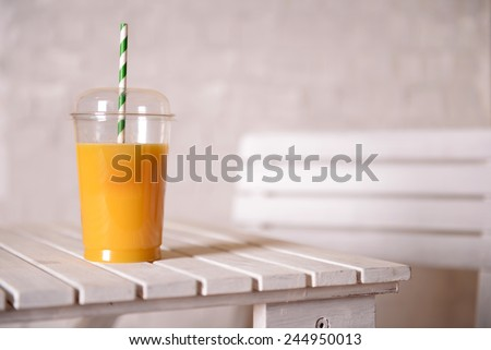 Orange juice in fast food closed cup with tube on wooden table and light wall background