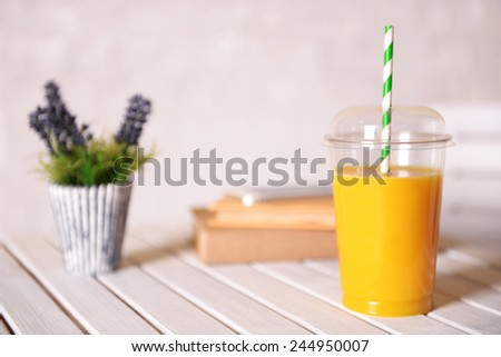 Orange juice in fast food closed cup with tube on wooden table with plant and light wall background