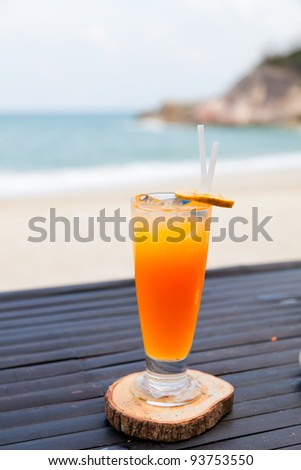 Orange juice in glass with ice, straw and fruit slice on ocean beach background