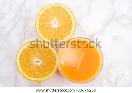 orange juice in the glass along with oranges cut, with ice, top