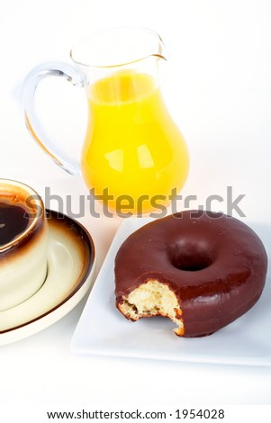 Orange juice jug and chocolate donut with a bite taken out, with coffee cup