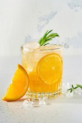 Orange juice or cocktail with rosemary and orange with ice in glass, cold summer lemonade on light gray slate, stone or concrete background. Beach concept with deep sun shadow. Top view.