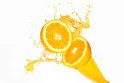 Orange juice splashing on half oranges against a white background