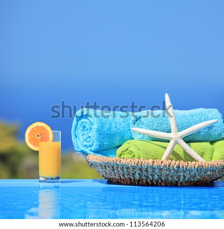 Orange juice, starfish and rolled up towels next to a swimming pool