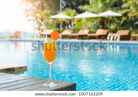 Orange juice with carrot slice in cocktail glass on wooden table at outdoor swimming pool, summer tropical holiday concept