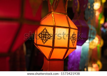 Orange Lanna lantern with background of other colorful lanterns in Loi Krathong festival