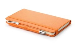 Orange leather notebook and ballpoint pen isolated on white