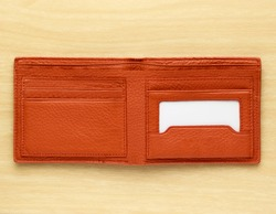 orange leather wallet on wooden board background