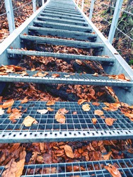 Orange leaves on steps of steel grate staircase to the rock view, former rock castle Falkenstejn or Sokoli castle from 13th century.