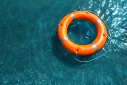 Orange life buoy floating in sea, above view. Emergency rescue equipment