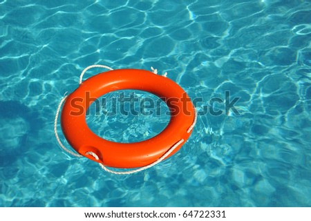 Orange lifebelt floating in blue water