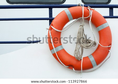 Orange lifebuoy and old rope hanging on a boat