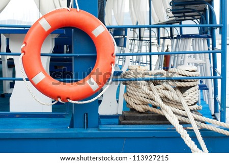 Orange lifebuoy and old rope hanging on the blue ship