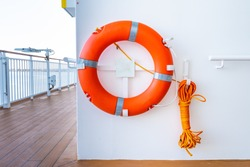 Orange lifebuoy or lifebelt emergency equipment device, hanging on ship exterior deck wall. Unmarked drowning overboard incident safety standard gear.
