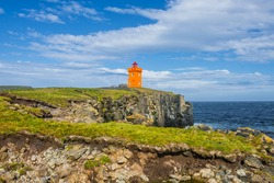 Orange lighthouse at the cost of Grimsey island nearby Iceland, summer, 2015