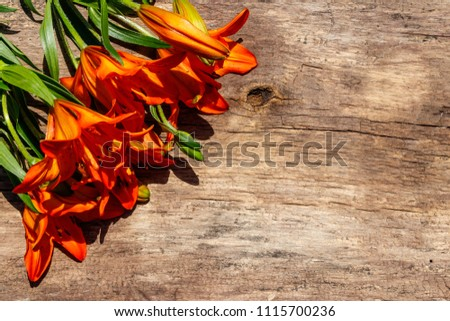 Orange lilies on rustic wooden background. Top view, copy space