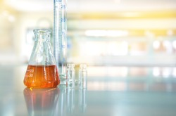 orange liquid in glass flask with cylinder vial in chemical science laboratory technology background