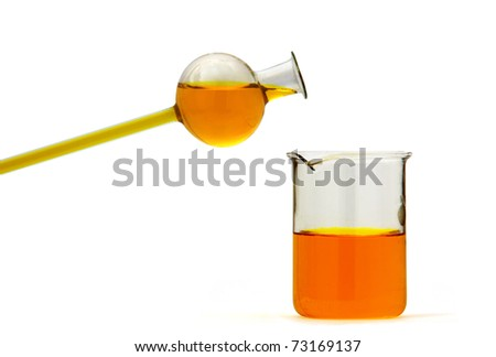 Orange liquid pured from thin vessel with spherical head to the 100 ml baker on white - stock photo