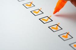 Orange marking on checklist box with pen, Checklist concept
