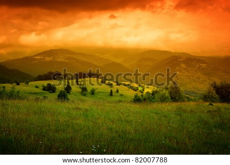 orange mist over mountains and cloudy sky