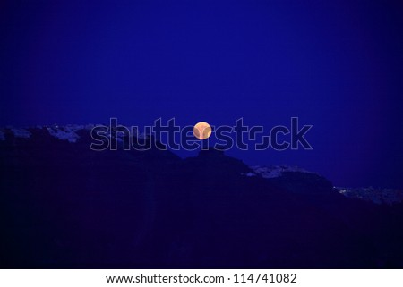 Orange moon over a silhouetted Santorini Greece