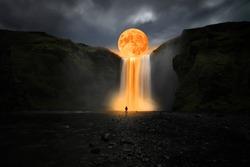 Orange moon over great waterfall