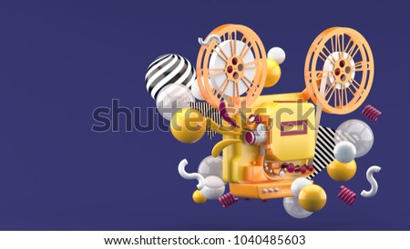 Stock Photo Orange movie projector amid colorful balls on purple background.-3d render.