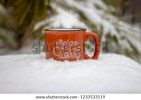 Orange mug hot beverage steam rising relax more worry less message on front surrounded by snowy scene and icy pine branches in winter background, holiday stress keep calm relax more worry less concept
