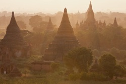 Orange mystical sunrise landscape view with silhouettes of old ancient temples and palm trees in dawn fog from balloon, Bagan, Myanmar. Burma