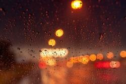 Orange night light bokeh from street light on traffic jam day. Rainy day. Transparent glass window with rain drop. Romantic weather. City life. Blur abstract background of urban light on rainy season