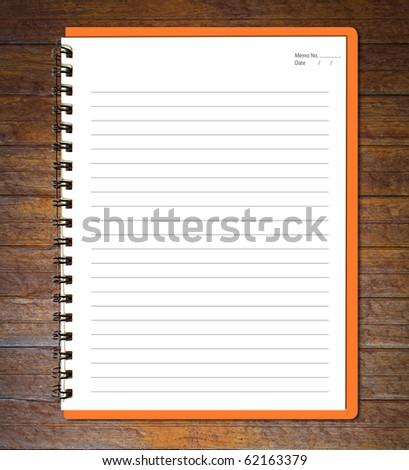 Orange notebook (blank paper) on wood wall.