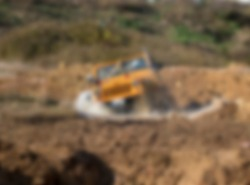 Orange offroad car with water blurred unfocused background in forest.