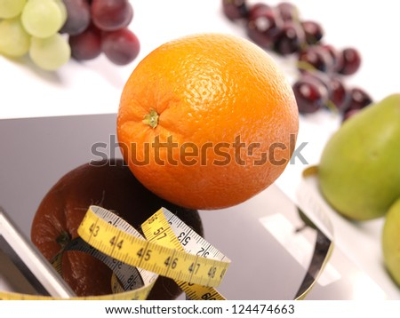 Orange on a scale with fresh fruits