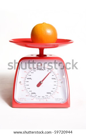 orange on kitchen food scale on white background