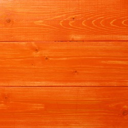 Orange paint coated wooden pine boards lying in a row as a close-up background composition