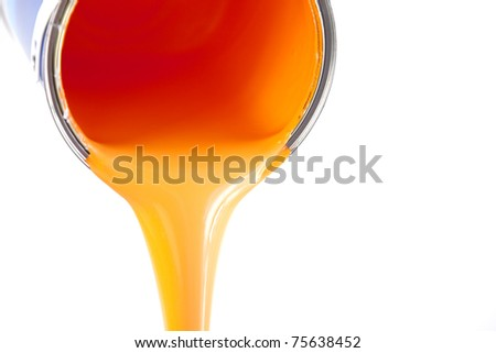orange paint flows from the bucket / isolated on white with copy space / photo